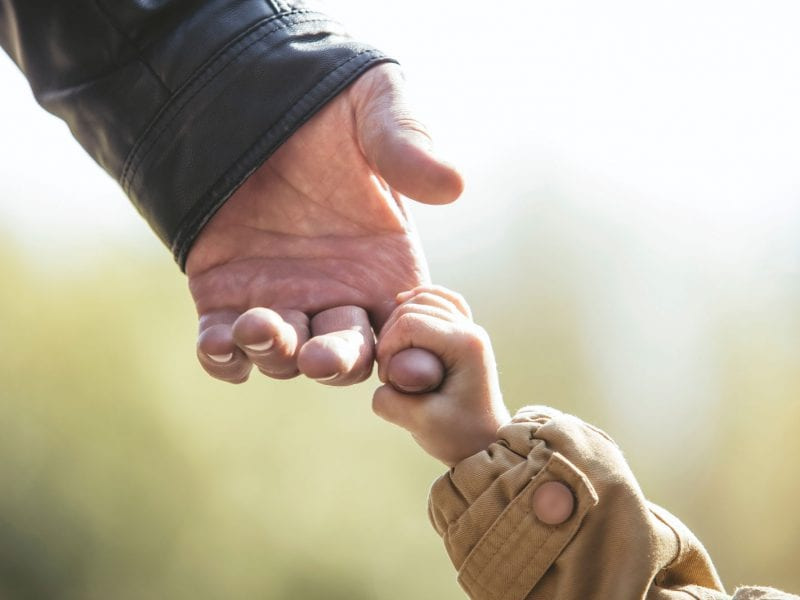 A child's hand grabs an older adult hand